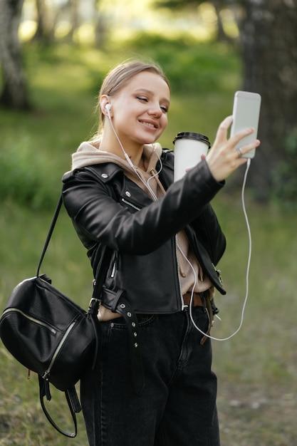 Une Belle Femme Dans Une Veste En Cuir Et Des écouteurs Se Promène Dans Le Parc Parle Sur Un Appel Vidéo Du Téléphone Sourit Et Boit Du Café Photo Premium