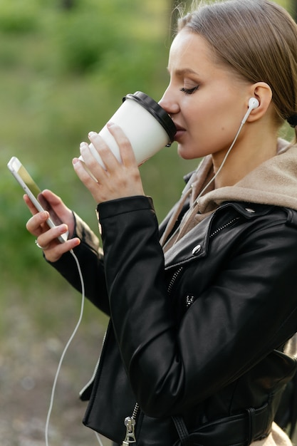 Une Belle Femme Dans Une Veste En Cuir Et Des écouteurs Se Promène Dans Le Parc Parle Sur Un Appel Vidéo à Partir D'un Téléphone Et Boit Du Café Photo Premium