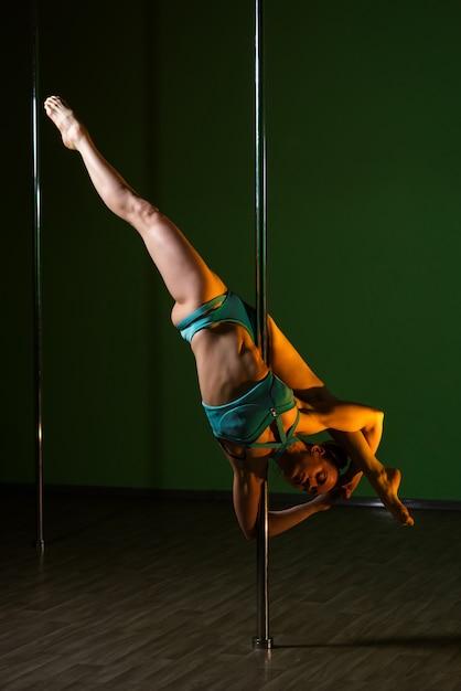 Belle femme danse près d'un poteau sur un fond coloré. Photo Premium