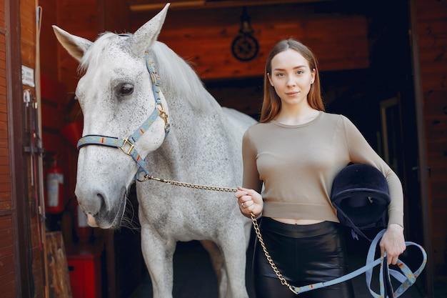 Belle femme debout avec un cheval Photo gratuit