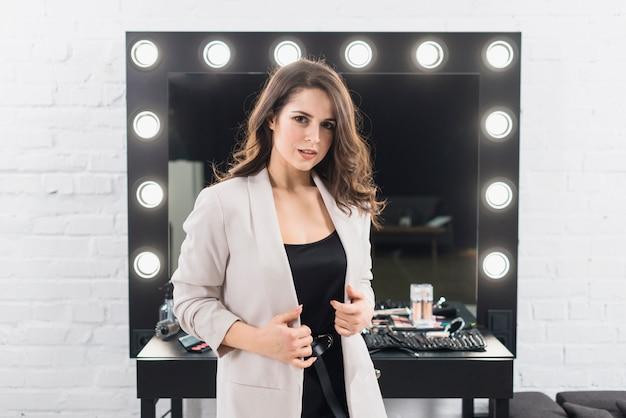 Belle femme debout contre un miroir de maquillage Photo gratuit