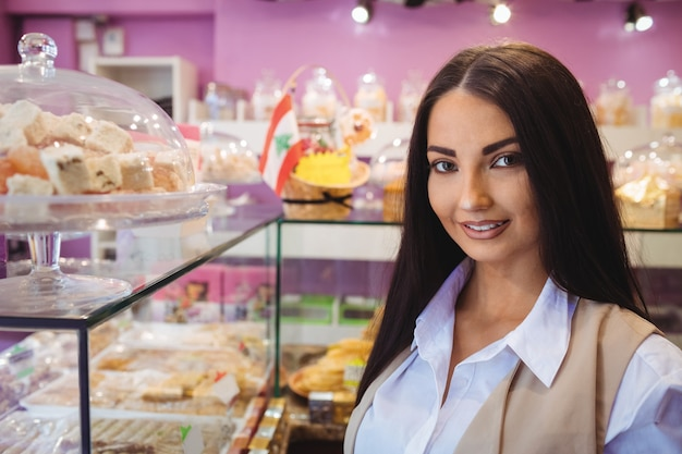 Belle Femme Debout Dans Une Boutique De Bonbons Turcs Photo gratuit