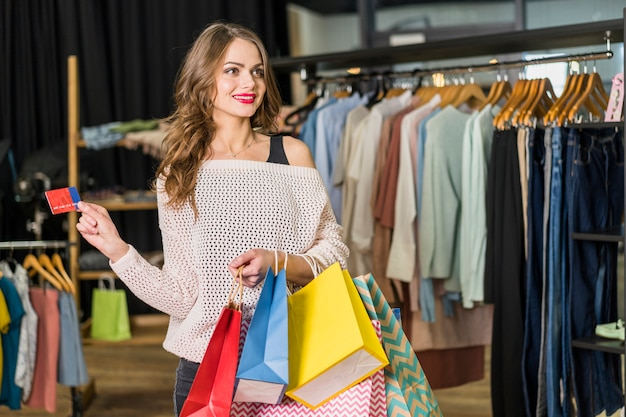 Belle femme, debout, dans, boutique, tenue, sacs provisions, et, carte de crédit, dans main Photo gratuit