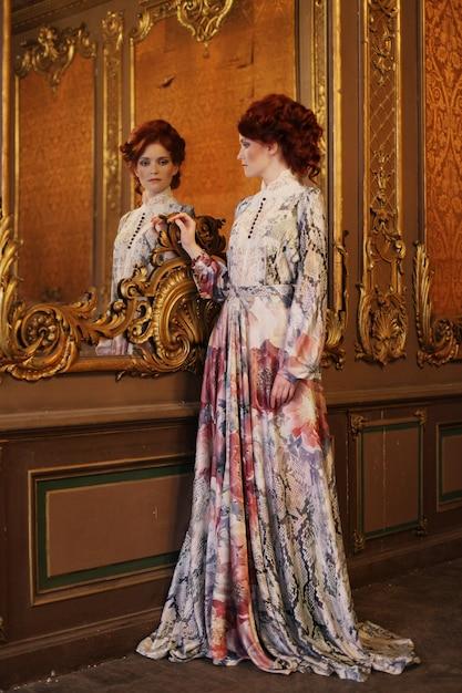 Belle femme debout dans la salle du palais avec miroir. Photo Premium