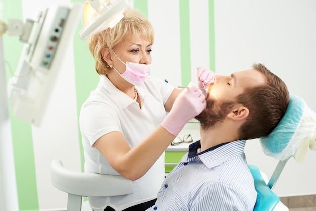 Belle Femme Dentiste Fréquentant Les Dents D'un Jeune Client Masculin De La Dentisterie Moderne. Photo Premium