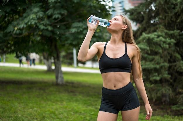 Belle femme eau potable coup moyen Photo gratuit