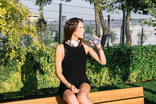 Belle femme de l'eau potable dans le parc Photo gratuit