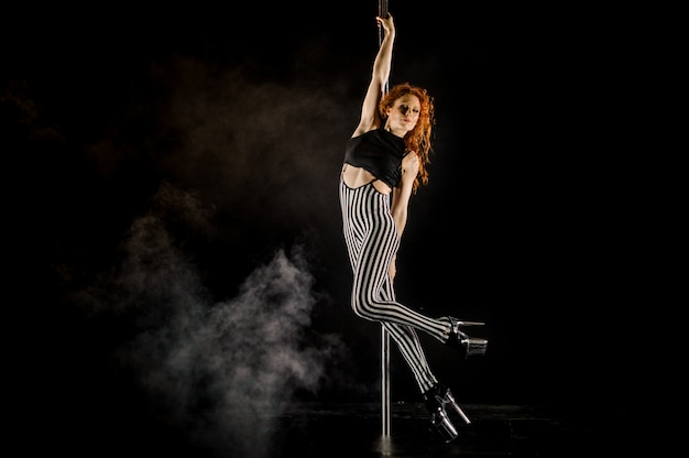 Belle femme effectuant pole dance sur pole Photo Premium