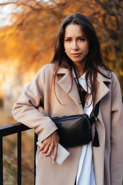 Belle femme élégante, debout dans un parc en automne Photo gratuit