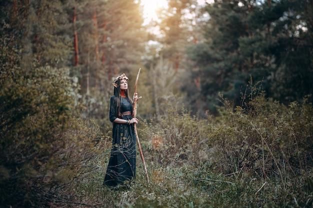 Belle femme elfe, forêt de féerie aux longues oreilles, couronne de couronne de cheveux longs et dorés sur la tête Photo Premium