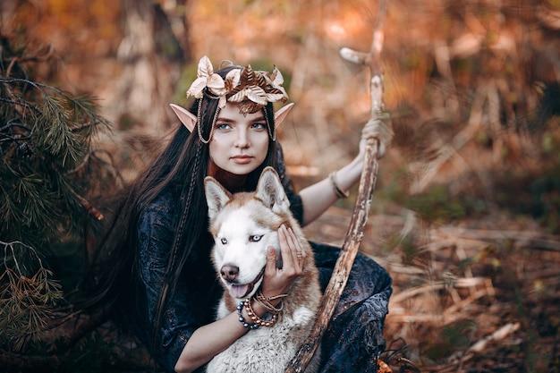 Belle femme elfe, forêt de féerie, couronne de guirlande dorée de longs cheveux noirs sur la tête avec chien rouge Photo Premium