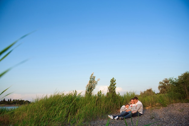 Belle femme enceinte avec sa famille assise au bord de la rivière. Photo Premium