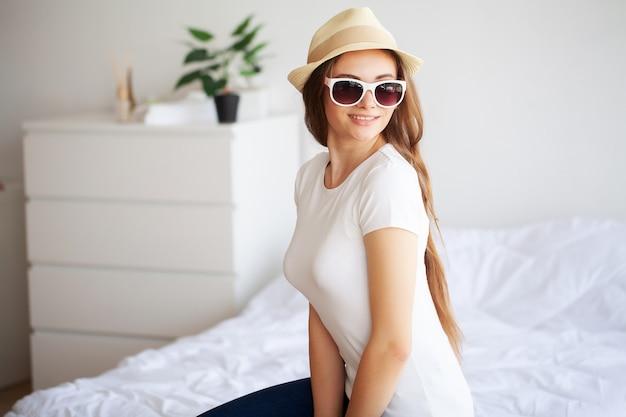 Belle femme est d'emballage des vêtements dans une valise à la maison. Photo Premium