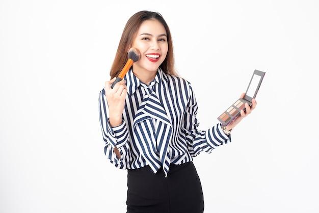 Belle femme est maquillage sur fond blanc Photo Premium