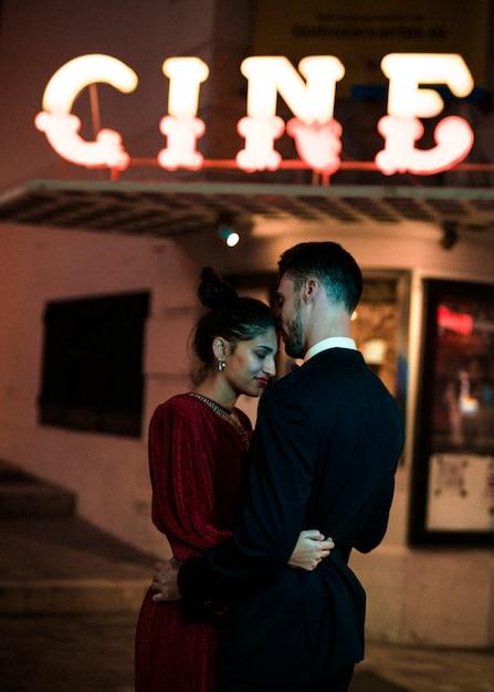 Belle femme étreignant avec jeune homme dans la rue en soirée Photo gratuit