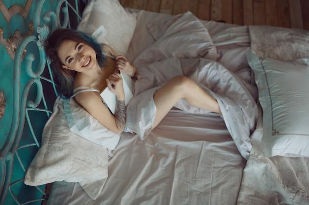 Belle Femme Excitée Souriante Lisant Un Livre Le Matin Photo gratuit