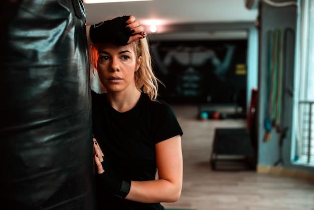Belle femme exitée se penchant sur le sac de boxe. Photo Premium