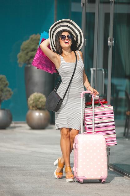 Belle Femme Faisant Du Shopping. Jolie Fille Tenant Des Sacs à Provisions Et Souriant. Dame Joyeuse Ayant Un Voyage. Photo Premium