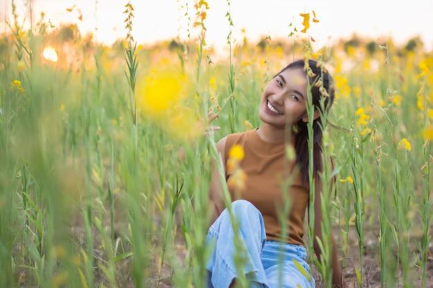 Belle femme avec fleur crotalaria pendant la soirée Photo Premium