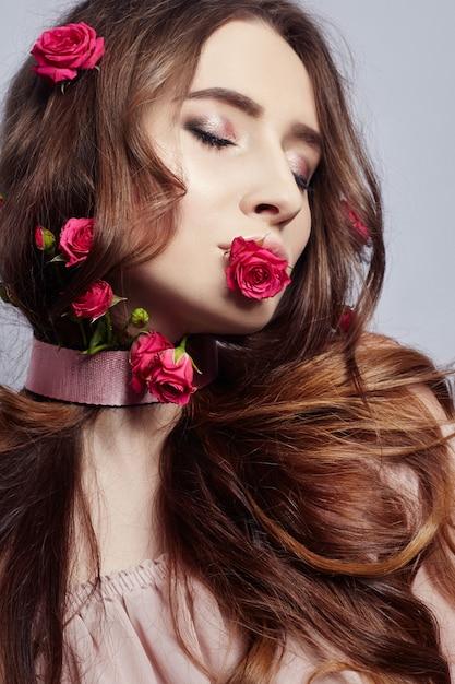 Belle femme avec des fleurs roses dans les cheveux longs Photo Premium