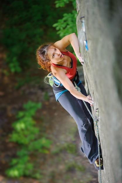 Belle femme grimpeur escalade raide rocher avec une corde Photo Premium