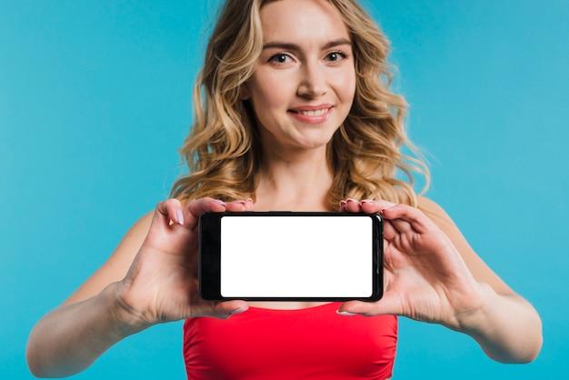 Belle femme en haut rouge montrant le téléphone mobile Photo gratuit
