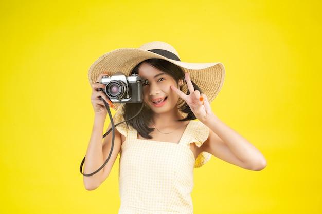 Une belle femme heureuse portant un grand chapeau et une caméra sur un jaune. Photo gratuit