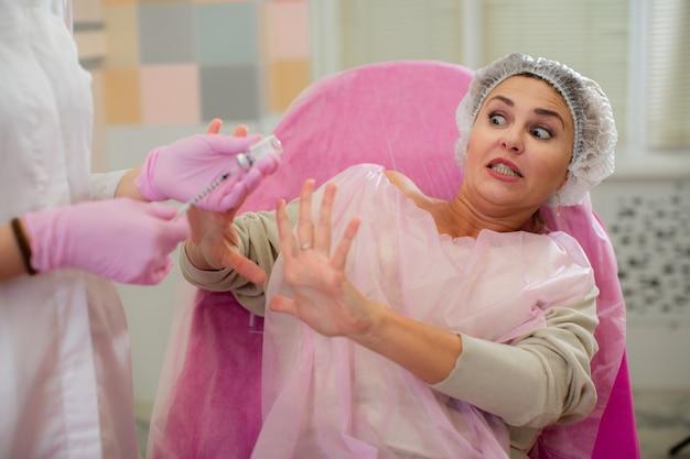 Une belle femme d'horreur se protège les mains de la seringue pour injection. Photo Premium