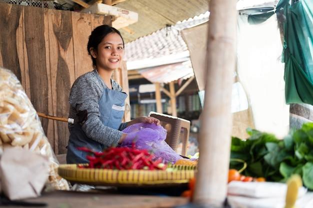 Belle Femme De Jardinier Sourit Alors Qu'elle Tire Une échalote D'un Sac à L'étal De Légumes Photo Premium