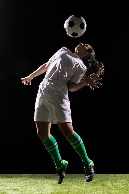 Belle femme jouant avec un ballon de foot Photo gratuit
