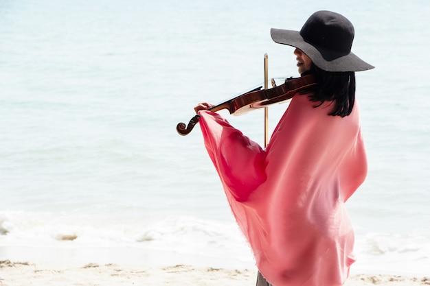 La belle femme jouant du violon sur la plage Photo Premium