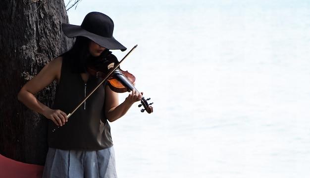 La belle femme jouant du violon sous l'arbre, pour se détendre Photo Premium