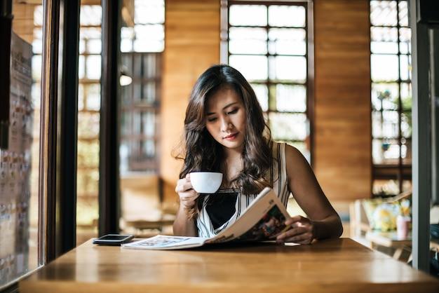 Belle femme lisant un magazine au café Photo gratuit