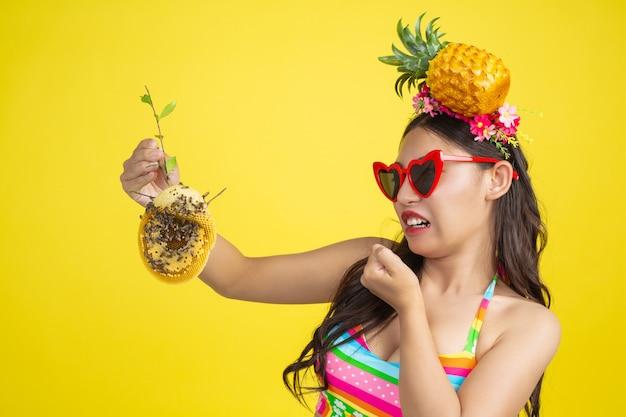 Belle femme en maillot de bain portant un nid d'abeille pose sur jaune Photo gratuit