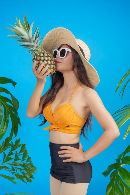Belle femme en maillot de bain tenant un ananas bleu Photo gratuit