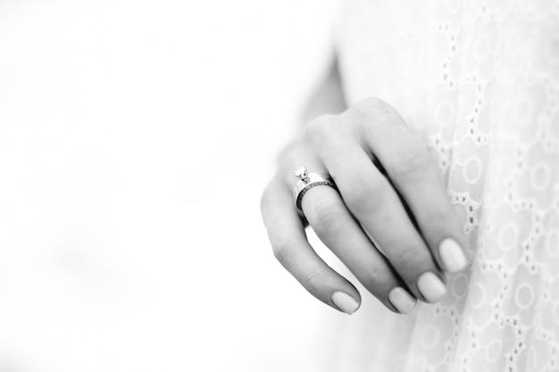 Belle femme à la main avec la bague de mariage sur fond d'océan. Photo Premium