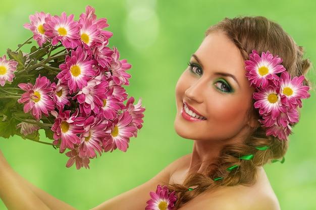 Belle femme avec maquillage et fleurs Photo gratuit