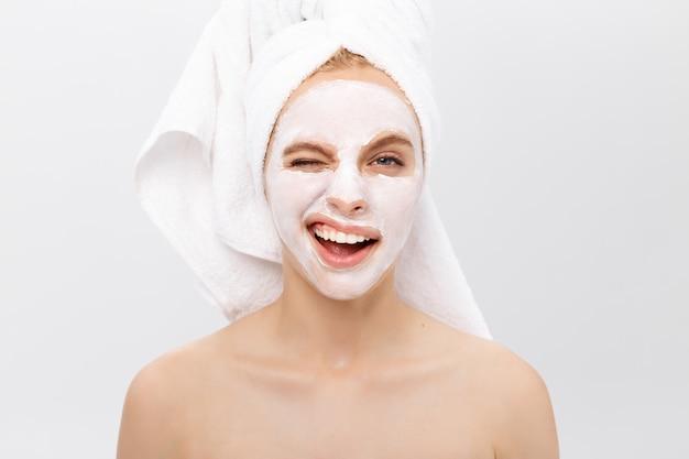Belle femme avec un masque facial sur fond blanc Photo Premium