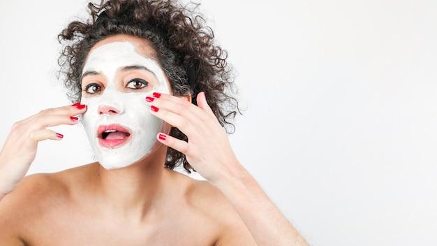 Belle femme avec masque facial isolé sur fond blanc Photo gratuit