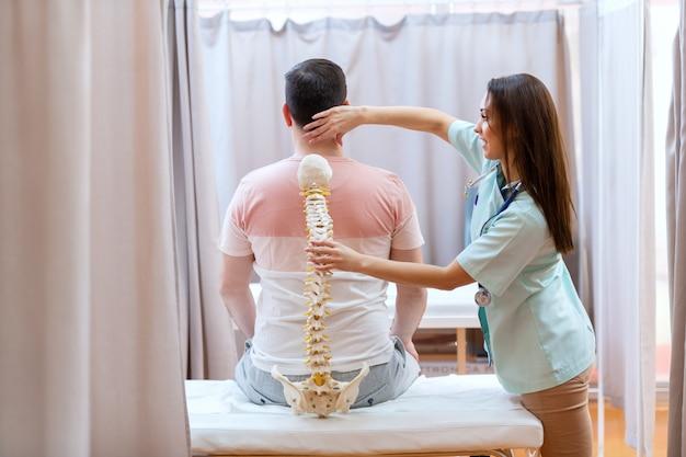 Belle Femme Médecin Tenant Le Modèle De La Colonne Vertébrale Et Examinant La Colonne Vertébrale Du Patient. Photo Premium