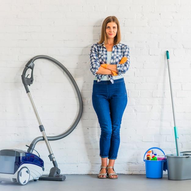 Belle femme de ménage avec la main pliée debout près des équipements de nettoyage Photo gratuit