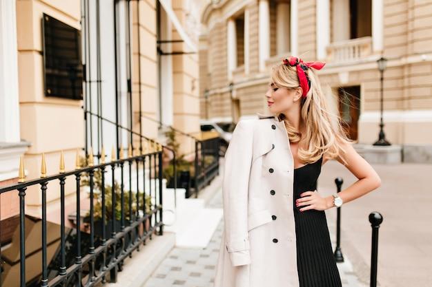 Belle Femme Mince En Robe Noire Posant Avec Plaisir Sur La Vieille Rue étroite Photo gratuit