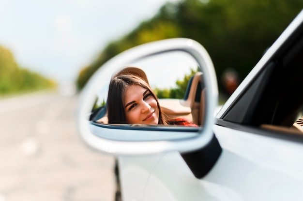 Belle femme sur le miroir de voiture Photo gratuit