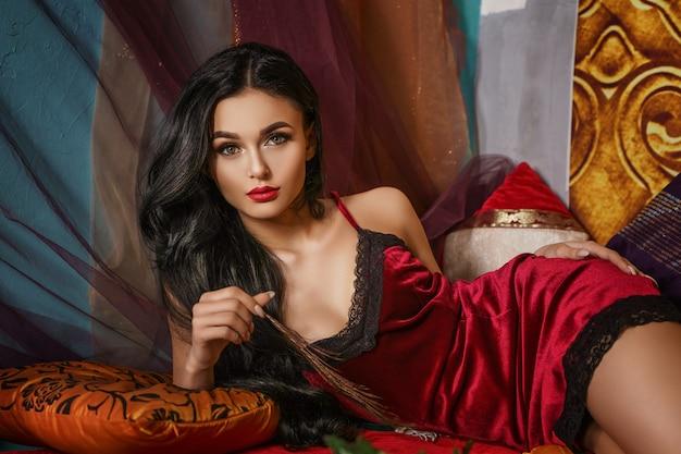 La belle femme à la mode se trouve dans un négligé rouge Photo Premium