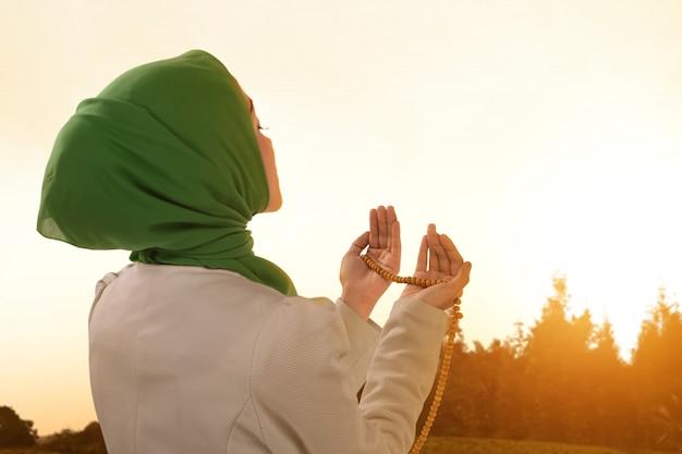 Belle femme musulmane asiatique priant avec des perles de prière Photo Premium