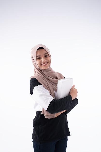 La belle femme musulmane embrassant le livre dans ses bras Photo Premium