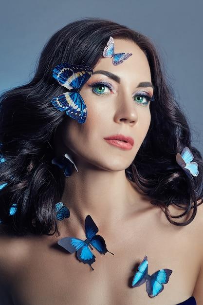 Belle femme mystérieuse avec des papillons bleus Photo Premium