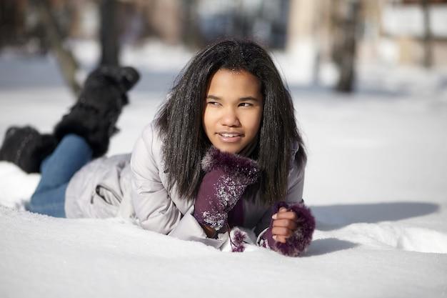 Belle Femme Noire Américaine Souriante Couchée Dans La Neige à L'extérieur Photo gratuit