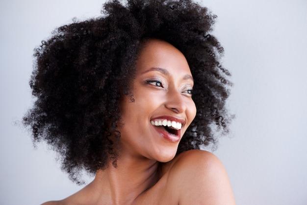 Belle femme noire aux cheveux bouclés en riant et en regardant loin Photo Premium