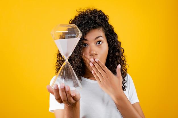 Belle femme noire avec sablier isolé sur jaune Photo Premium